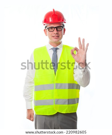 Young man using a yellow vest and red helmet. Doing the ok sign and smiling