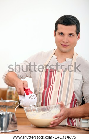 young man using an electric egg beater - stock photo