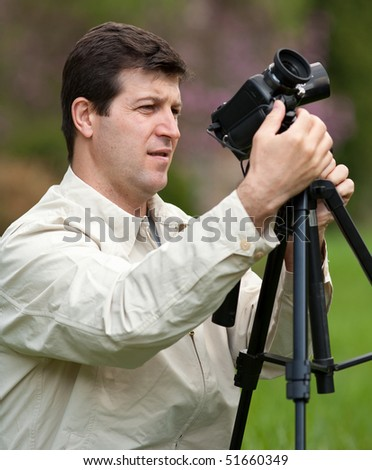 Young man using camcorder on a tripod outdoors in a forest - stock photo