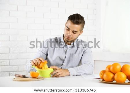 Young man using citrus-fruit squeezer, preparing orange juice - stock photo