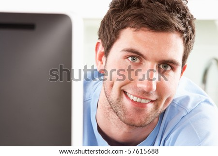 Young Man Using Computer In Modern Kitchen - stock photo