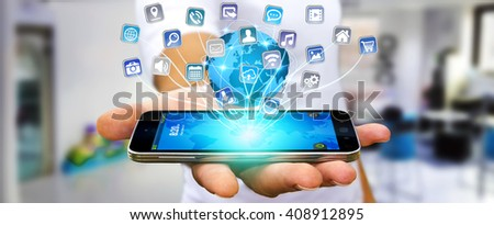 Young man using digital application with icons flying over his mobile phone - stock photo