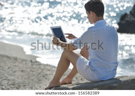 Young man using Digital Tablet on the beach - stock photo