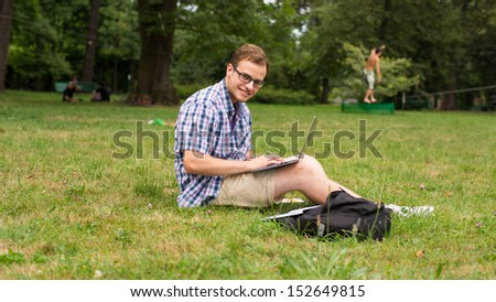 Young man using his laptop on the grass.