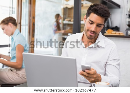 Young man using laptop and mobile phone in the coffee shop - stock photo