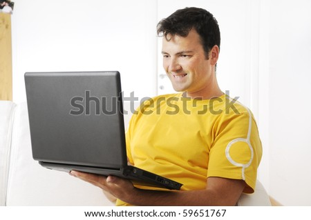young man using laptop and smiling. Indoor with white background