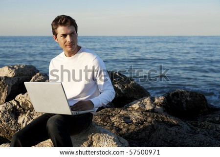 Young man using laptop at beach - stock photo