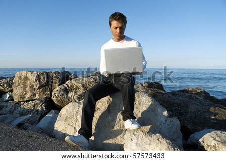 Young man using laptop at beach, blue sky and ocean in background - stock photo