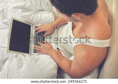 Young man using laptop at the bedtime - stock photo