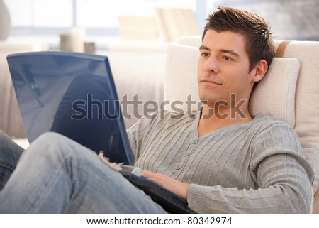 Young man using laptop computer at home, looking at screen, smiling.? - stock photo