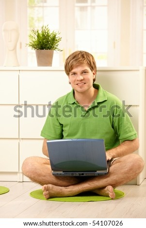 Young man using laptop computer, sitting on living room floor, smiling at camera .