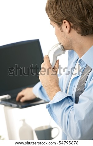 Young man using laptop computer while shaving. Isolated on white - stock photo