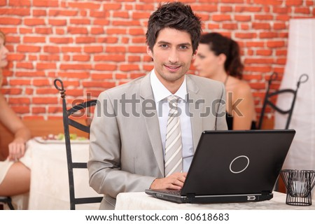 Young man using laptop in a restaurant - stock photo