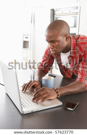 Young Man Using Laptop In Modern Kitchen - stock photo