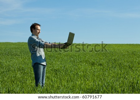 young man using laptop in the field - stock photo
