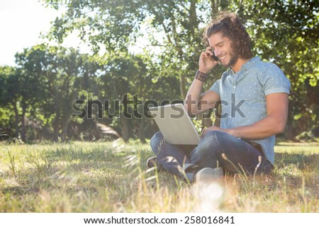 Young man using laptop in the park on a summers day - stock photo