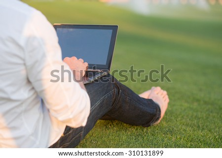 Young man using laptop in the park outdoors. Man typing and sitting on the green grass. - stock photo