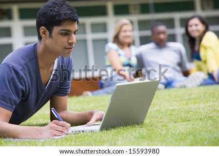 Young man using laptop on campus lawn, with other students relaxing in background - stock photo
