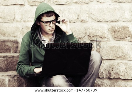 Young man using laptop on the steps - stock photo