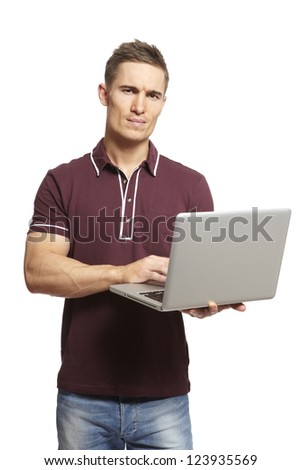Young man using laptop on white background looking confused