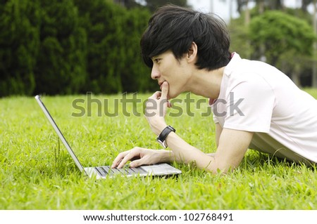 Young man using laptop outdoors - stock photo