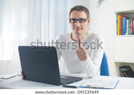 Young man using laptop showing ok sign