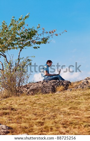 young man using laptop sitting on a hill against the blue sky - stock photo