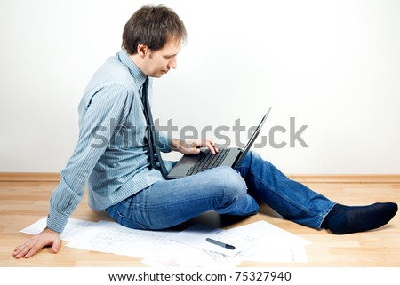 young man using laptop sitting on the floor in the room - stock photo