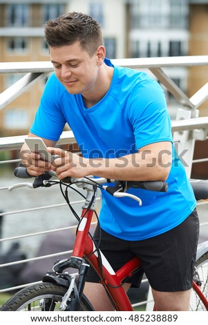 Young Man Using Mobile Phone Whilst Out On Cycle Ride