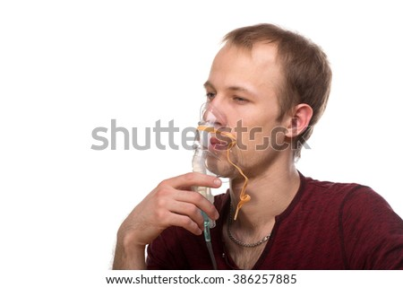 Young man using nebulizer mask for respiratory inhaler Asthma Treatment isolated on a white background. Close up view. - stock photo