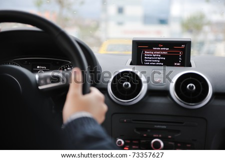 young man using new car navigation and onboard vehicle transport system - stock photo