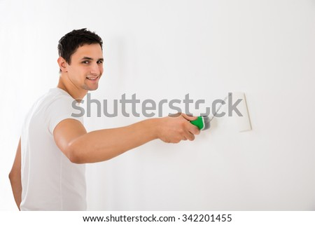 Young man using paint roller on white wall at home - stock photo