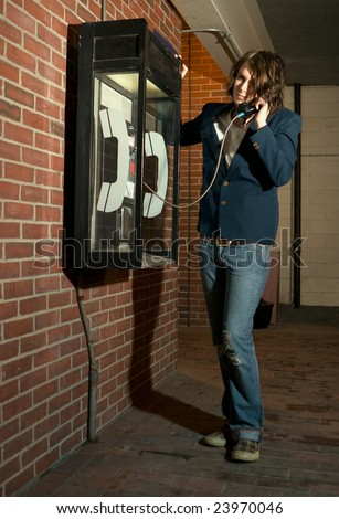 Young man using payphone - stock photo