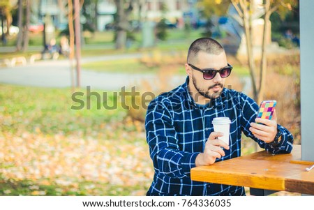 Young man using smartphone and relaxing outdoor.