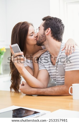 Young man using smartphone while girlfriend kisses him at home in the kitchen - stock photo