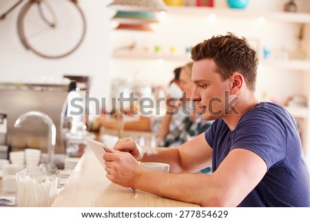 Young man using tablet computer in a cafe - stock photo