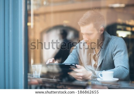 Young man using tablet computer in coffee shop