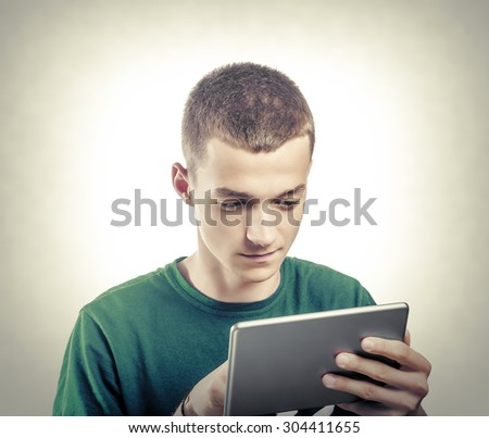 Young man using tablet computer. Toned photo. - stock photo