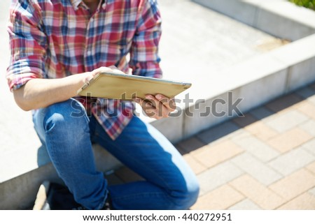 Young man using tablet in the park - stock photo