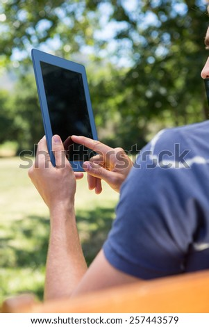 Young man using tablet on park bench on a summers day