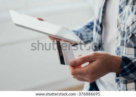 Young man using tablet while holding credit card. Shopping online concept - stock photo