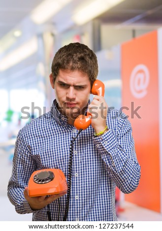 Young Man Using Vintage Telephone at a mall