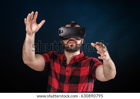 Young man using VR glasses headset trying to touch objects in virtual reality.