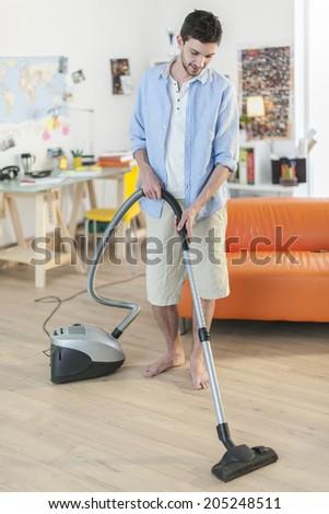 young man vacuuming home - stock photo