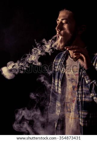 Young man vaping and make circles.Black Background - stock photo