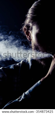 Young man vaping with RDA. Black Background - stock photo