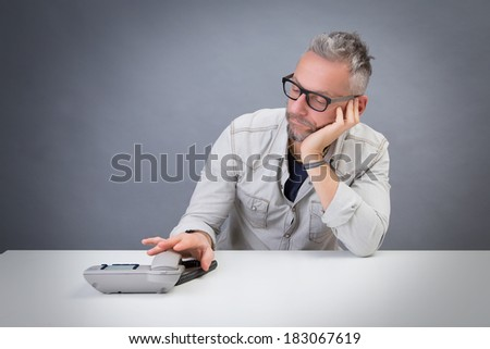 young man waiting for a call: studio portrait - stock photo