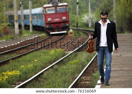 Young man waiting for the train in a rural railway station - stock photo