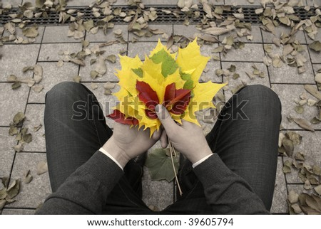 Young man waiting in autumn park with autumn leaves bouquet