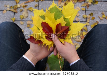 Young man waiting in autumn park with colorful autumn leaves bouquet